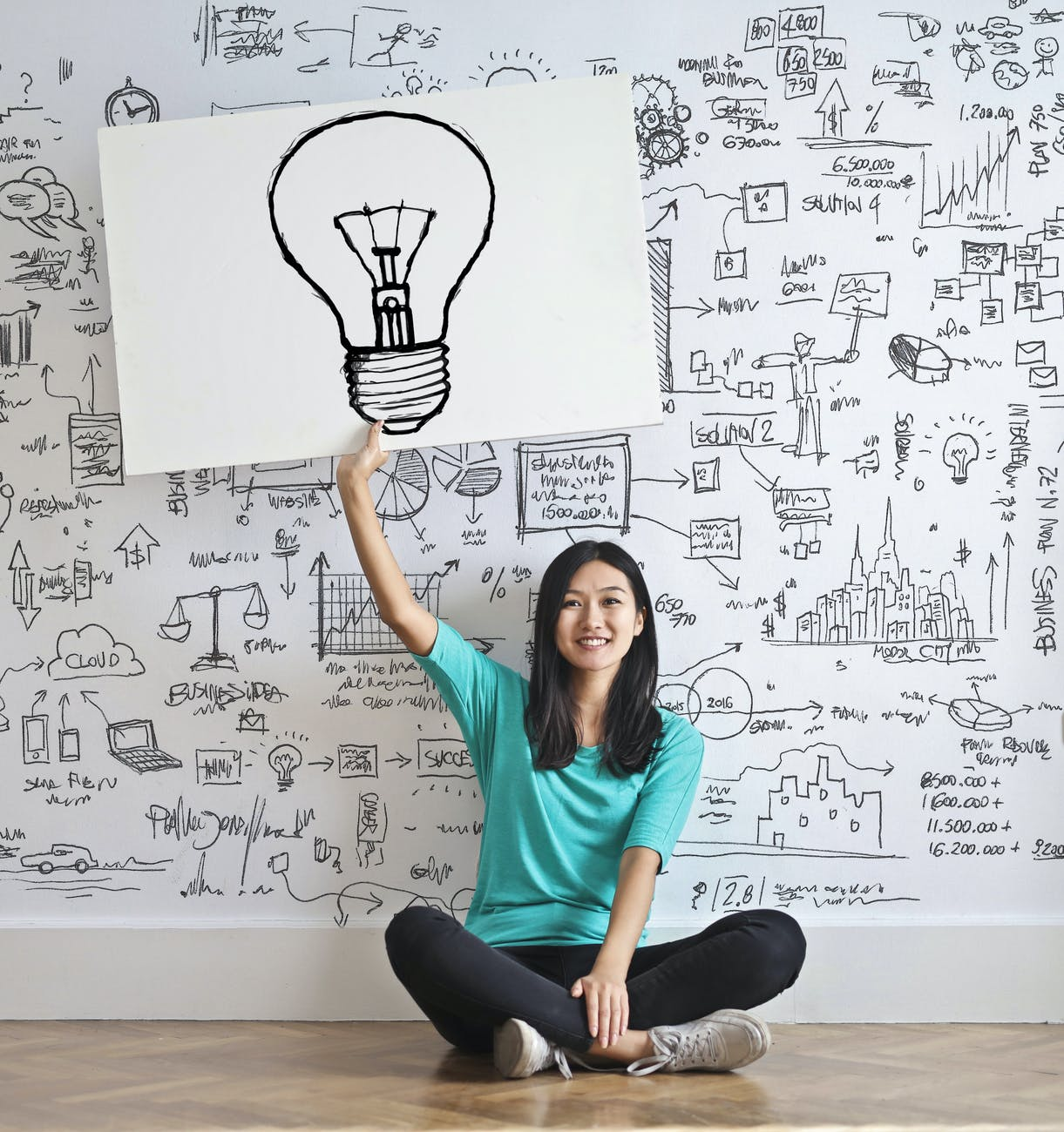An image of a girl holding up a placard of a bulb. The background of the image has a number of graphs, equations, pie charts, etc. drawn on a white wall.